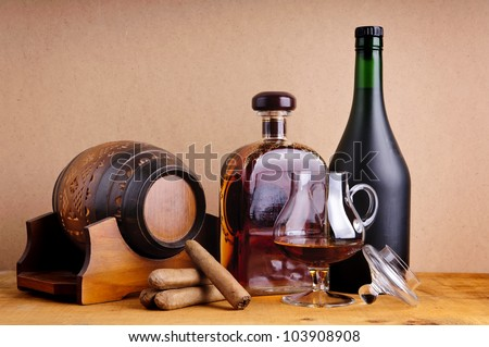 cuban cigars and cognac in glass, bottles and barrel on a wooden background