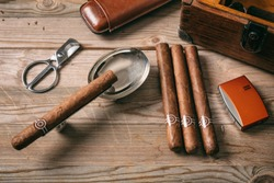 Cuban cigars and smoking accessories on wooden background, top view