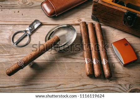 Cuban cigars and smoking accessories on wooden background, top view #1116119624