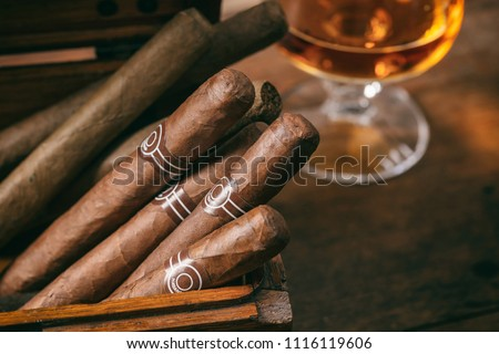 Cuban cigars in a wooden box, blur glass of cognac brandy, closeup view with details, copy space