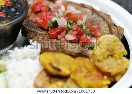 Cuban dinner consisting of rice, beans, plantains, and beef steak.