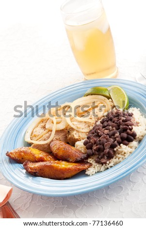 Cuban dinner of roast pork, black beans & rice, and sweet plantains, served with a glass of iced tea.