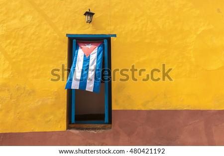 Shutterstock Cuban flag hanging on a door in Trinidad, Cuba