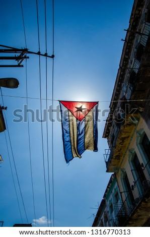 Cuban flag hangs in a street of the working-class neighborhood of Central Havana #1316770313