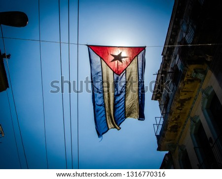 Cuban flag hangs in a street of the working-class neighborhood of Central Havana