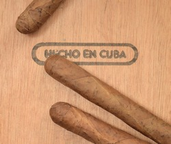 Cuban handmade tobacco cigars on wooden cedar box with text on spanish