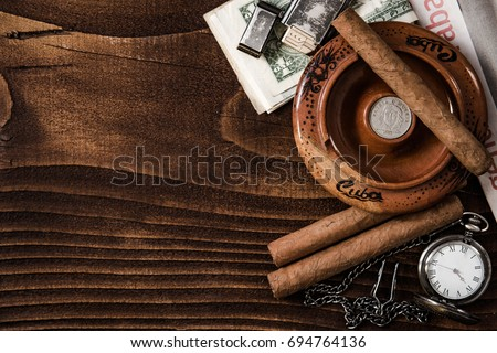 Cuban items,cigars, money, ashtray and vintage watch on wooden table