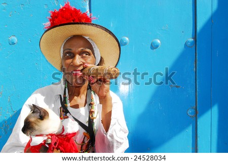 Cuban lady with siamese cat and big cigar in the streets of Havana, Cuba