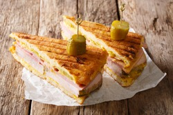 Cuban sandwich with ham, mustard, cheese, pickled cucumbers and pork close-up on paper on the table. horizontal