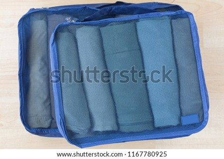 Cube meshed bags with rolled clothes, t-shirt, pants. Set of travel organizer to help packing luggage easy, well organized