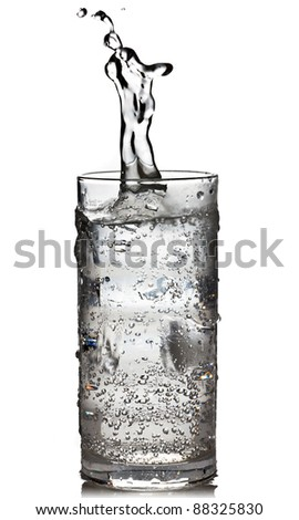 Cube of ice dropped into the glass of sparkling water with splash