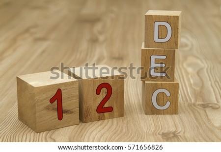 Cube shape calendar for DECEMBER 12 on wooden surface.  #571656826