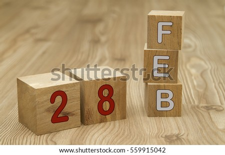 Cube shape calendar for February 28 on wooden surface with empty space for text. #559915042