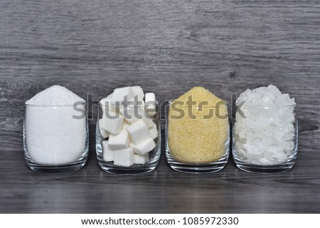 Cube sugar, raw sugar , crystalline sugar and granulation sugar in clear glasses with grey wooden background