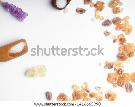 Cube sugar, raw sugar , crystalline sugar and granulation sugar in white background, wooden spoon