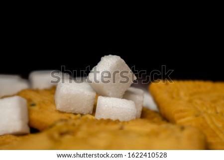 Cube sugar, raw sugar , crystalline sugar and granulation sugar with cookies on black background