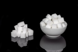Cube sugar, sugar cubes in a round dish, and stacked against a black background, with mirroring