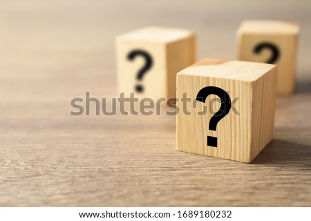 Cube with question mark on wooden background. Space for text