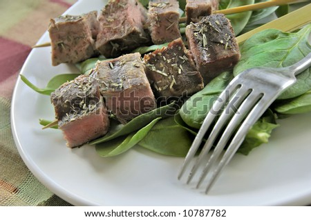 Cubed and skewered steak on a bed of spinache leaves.