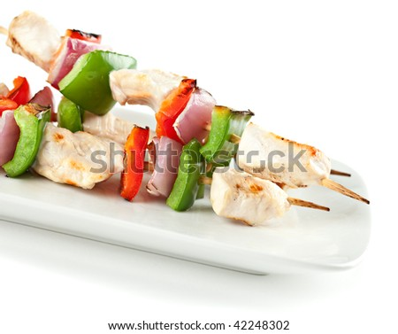 cubed chicken kabobs with red peppers, green peppers and red onion on isolated background