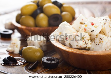 Cubed feta cheese with olives in olive wood bowl and green and black olives on rustic wooden background.  Selective focus.