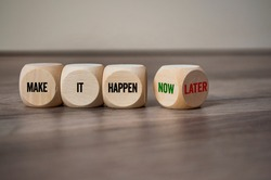 Cubes and dice showing the words Make it Happen on wooden background