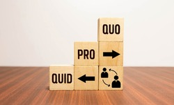 Cubes and dice with business message quid pro quo on wooden background.