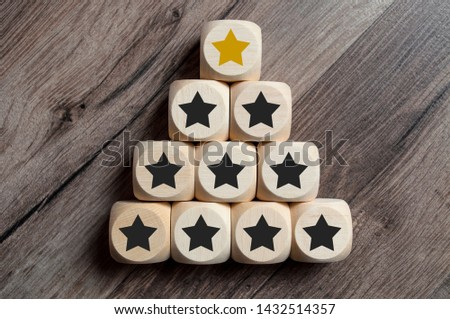 Cubes and dice with golden star on top of a pyramide