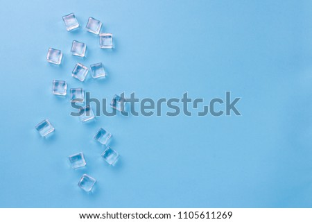Cubes of ice on a light blue background. Flat lay, top view.