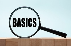 Cubes on a light blue wooden background. On them a magnifying glass with the word BASICS