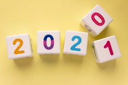 Cubes with colorful numbers on a yellow background. Year change concept, late 2020 and early 2021. Digit 1 pops out digit 0. New year, calendar