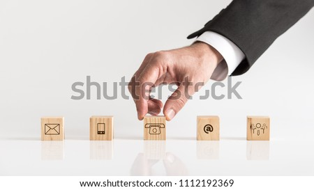 Cubes with contact symbols - envelope, at sign, telephone and human icon being placed on a white table by a businessman conceptual of communication and customer support.