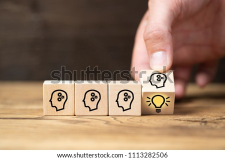 cubes with head symbols and hand that flips one revealing an idea