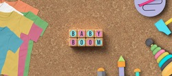 cubes with message BABY BOOM and toys and clothes on cork background