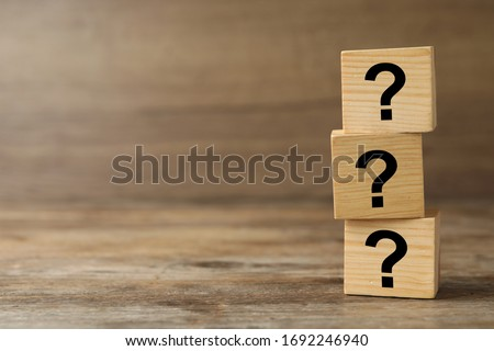 Cubes with question marks on wooden background, closeup. Space for text