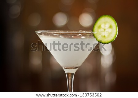 cucumber martini served on a bar top garnished with a cucumber slice
