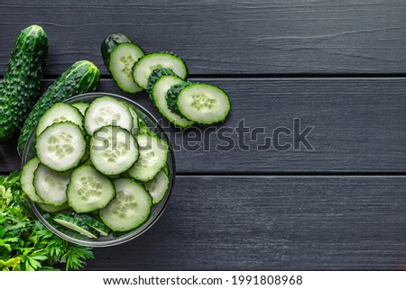 Cucumber on  dark wood texture background.Cucumbers harvest in summer. Cucumbers for salads or canning. Summer vegetables.Slices of fresh cucumbers in a bowl.