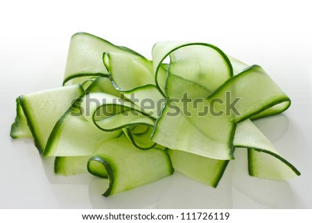 Cucumber shavings arranged attractively in a pile on a white surface - stock photo