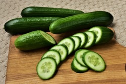 Cucumber sliced on the cutting board, salad ingredient, fresh cucumbers on a table.