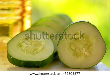 Cucumber slices and bottle of vinegar.