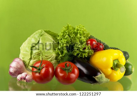 cucumbers, greens, eggplants, vegetable marrows cabbage and tomatoes on a green background