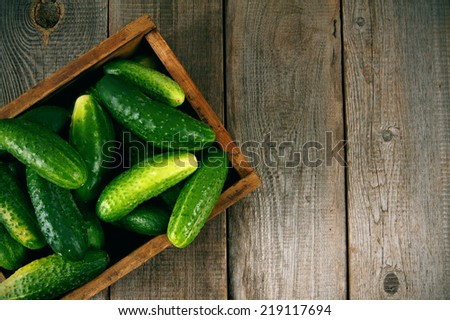 Cucumbers in a box on a wooden background.