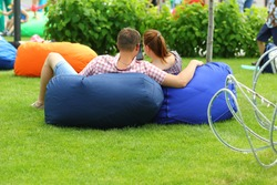 Cuddling couple on bean bags enjoy picnic in the park