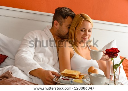 Cuddling young couple romantic morning in bed drinking coffee