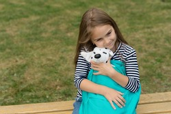 Cuddly little plaything. Small kid cuddle toy dog in bag