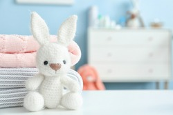 Cuddly toy with clothes on table in children's room