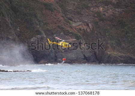 CUDILLERO, SPAIN - OCTOBER 8: Fire rescue helicopter refill bucket in the sea, goes to a fire in Cudillero,  on October 8, 2011 in Cudillero, Spain