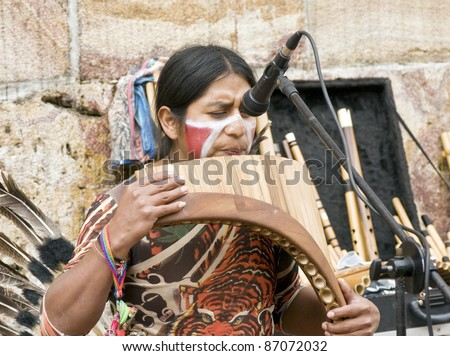CUENCA, ECUADOR - MAY 27: Andean Indian plays traditional instruments on May 27, 2011 in Cuenca, Ecuador. Indigenous descendants are found in the towns of the Andes mountain range in South America.