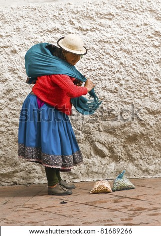 CUENCA, ECUADOR - MAY 27: Indigenous woman packs up her fruits after selling on a market street on May 27, 2011 in Cuenca, Ecuador.She sells mostly hand crafted items, flowers and fruits.
