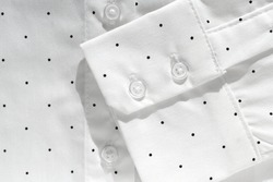 Cuffs. Two-button cuff on a white organic cotton shirt with black polka dots. Details of modern clothing